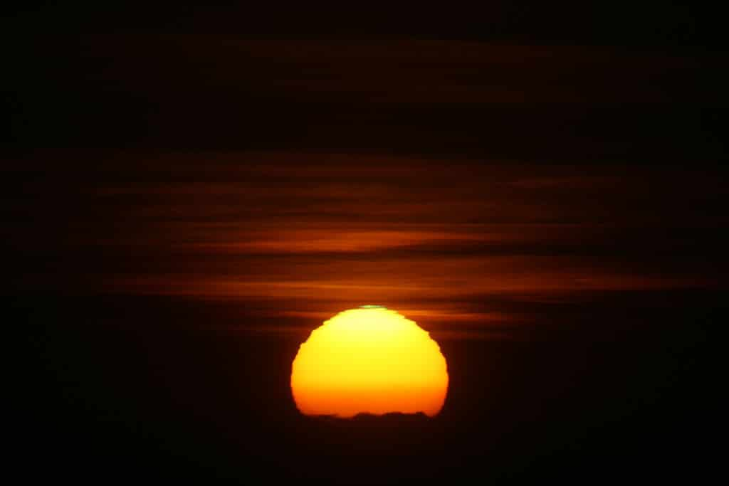 "Atmospheric refraction distorts the Sun's disk when it is low to the horizon. The unevenness of the distortion is due to variations in the atmosphere. Photo Credit : Brocken Inaglory (https://commons.wikimedia.org/wiki/File:Green_flash_121007.JPG), ""Green flash 121007"", https://creativecommons.org/licenses/by-sa/3.0/legalcode"