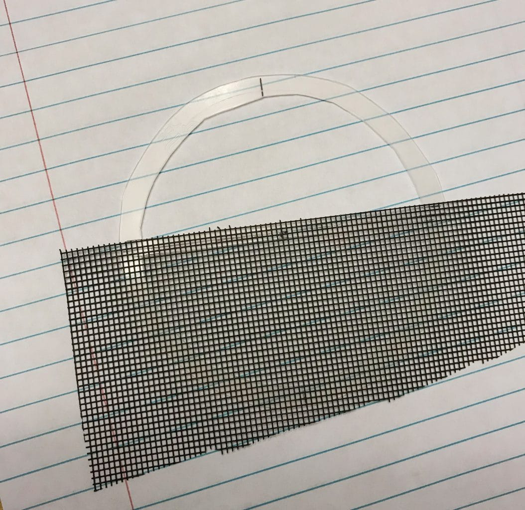 I've lined the screen up on the bottom portion of the mask with the center line I drew. (And not with the rules on the paper.) I'm using a sheet of paper to keep any stray superglue from getting on my table.