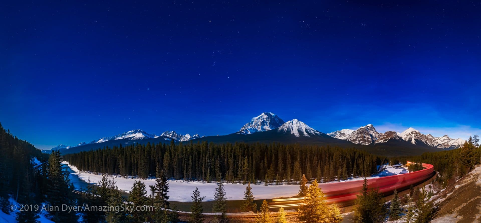 Alan Dyer / AmazingSky.com A panorama of Morant's Curve, a famous viewpoint on the Bow River in Banff National Park, with an eastbound train on the CPR tracks under the stars of the winter sky. Illumination is from the 13-day gibbous Moon off frame at left.  Orion is at centre; Sirius and Canis Major at left; and Taurus and the Pleiades at right. The main peak at centre is Mount Temple; the peaks at right are the ones around Lake Louise.  I shot this March 19, 2019 at the start of the evening, from the new viewpoint on the Bow Valley Parkway. Morant's Curve is named for the famed CPR photographer Nicholas Morant who often shot from here with large format film cameras.  Now, how did I do this? I was shooting multi-segment panoramas at the viewpoint when a train whistle in the distance to the est alerted me to the oncoming train. I started the panorama segment shooting at the left, and just by good luck the train was in front of me at centre when I hit the central segment. I continued to the right to catch the blurred rest of the train snaking around Morant's Curve. It took some adjustments of the masks in the panorama segments to get the train to blend well from segment to segment. This was stitched with PTGui as Photoshop would not handle this well. PTGui allows adjusting the masks on the individual segments. The equirectangular projection used stretches out and distorts the constellations a bit at top.  Each segment is 8 seconds at f/3.2 and ISO 800 with the 24mm Sigma Art lens and Nikon D750 in portrait orientation. I added a Luminar Orton glow effect to the ground for artistic effect.