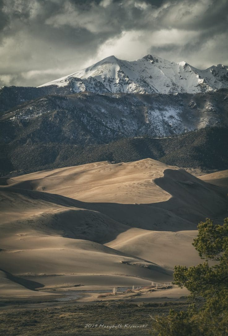 2019 Copyright MaryBeth Kiczenski. Golden hour light hitting the dune field.  These towering dunes look small next to the 14,000-foot mountain peaks!  Medano Creek flows ever so slightly in the foreground.  The creek is a result of the snowmelt in the mountains.  This season, according to the park,  was 178% above normal, so I expect this creek to be a river by the time this article is released. (May)