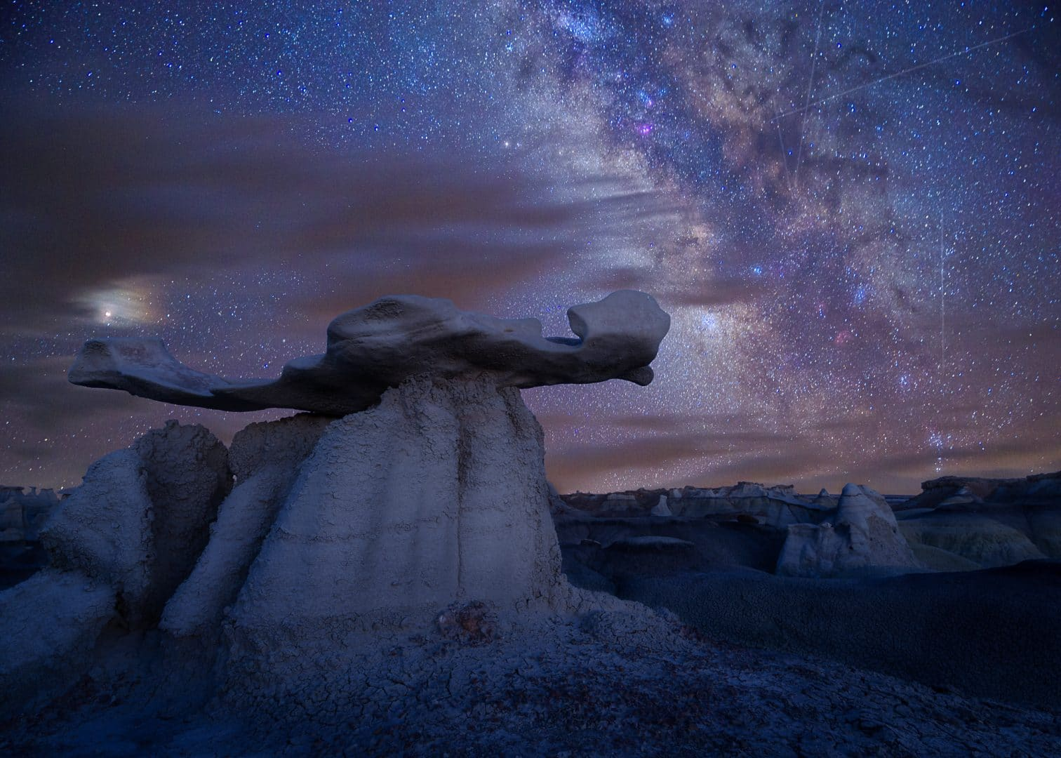 """A focal length blend taken by Aaron Martinez in Bisti Badlands. Foreground: 20mm, f/11, 4 sec, ISO 100 Sky: 35mm, f/2.8, 70sec, ISO 2200. From MilkyWayPhotographers.com, """"Top Milky Way Photography Tricks That Aren't Tricks!"""""""