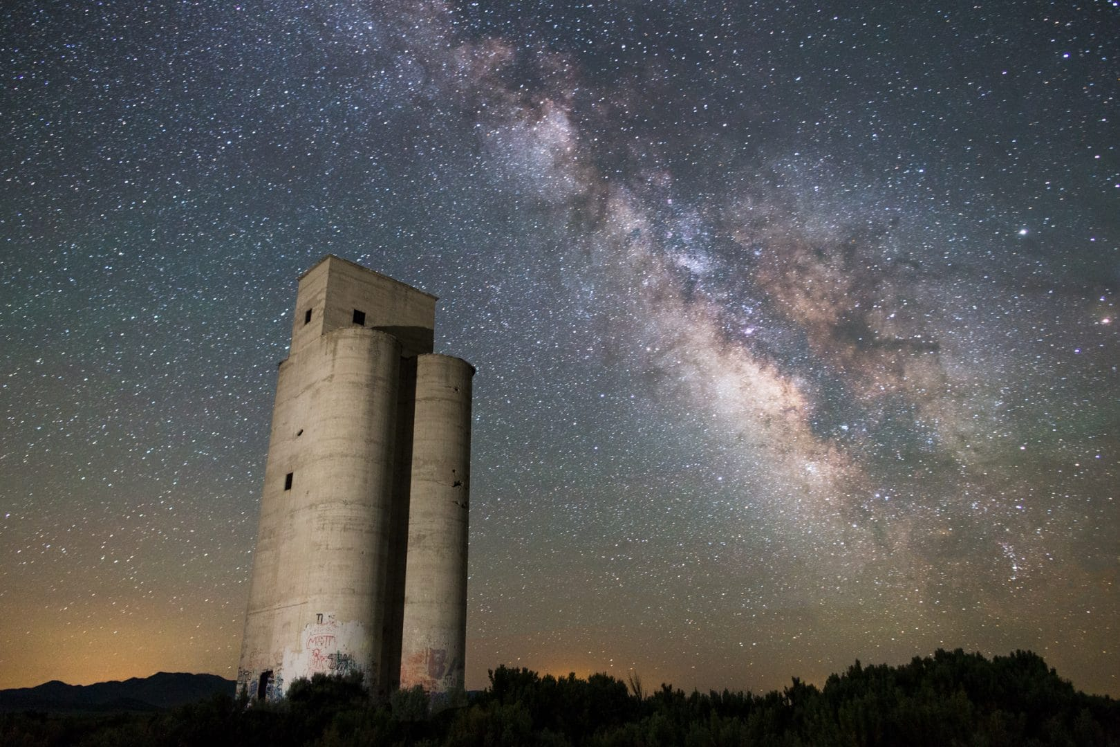 Milky Way over a tall abandoned silo showing the benefits of composition tip for Milky Way Photography number 1: Make sure you have an interesting tall subject that can break the planes of the rule of thirds in your composition.